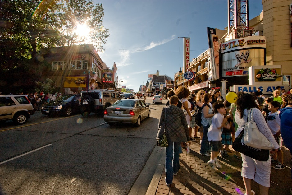 Clifton Hill, Niagara Falls, teamed with vacationers of the long weekend in the United States, as the Sun begins to set behind buildings