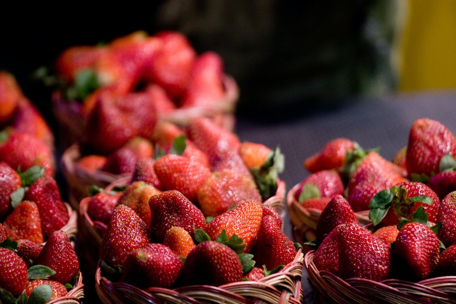 Strawberries for sale in the market, at $1 for each basket.