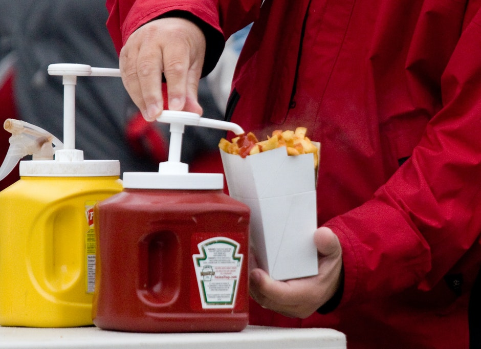 A man applies ketchup onto his serving of fresh-cut fries.