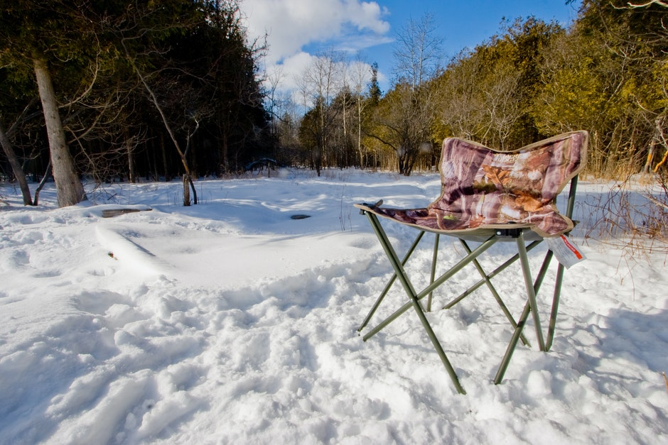 A foldable seat in snow in the middle of a jungle.